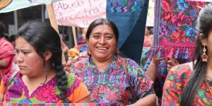 Woman smiles holding a sign at the international women's day march in Guatemala in 2017