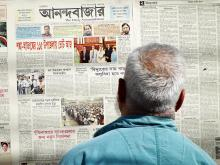 Man reads newspaper on wall - Dhaka, Bangladesh